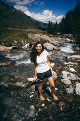 Junge Frau steht in eiskaltem Bergbach und lächelt