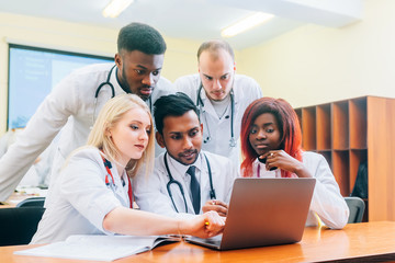 Multiracial team of young doctors working on laptop computer in medical office.