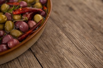 Cropped image of olives with oil and chili pepper in container