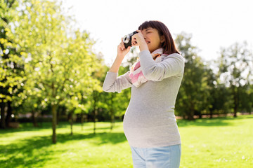 happy pregnant asian woman with camera at park