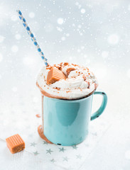 Christmas mood!) Hot chocolate with cream, cinnamon and a toffee in a blue vintage mug on a light background. The best celebration background. Winter xmas holidays concept.