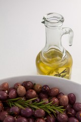 Olives with rosemary in bowl by oil jar
