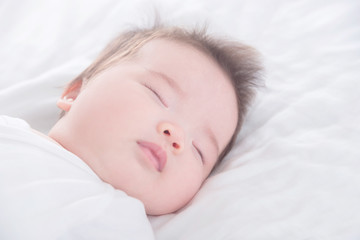 Closeup little asian baby girl wearing white cloth sleeping on white bed