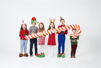 Happy children holding huge candy cane .