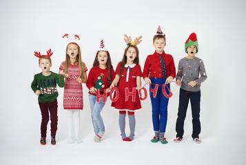 Happy children singing christmassy carols