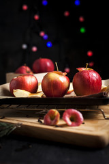 cooking of baked apples for New Year's holidays, Christmas tree and New Year's lights, honey and cinnamon on a wooden cutting board on a dark background