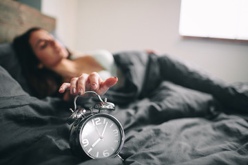 Young sleeping woman and alarm clock in bedroom at home. Girl overslept in bed and looking alarm clock in shock