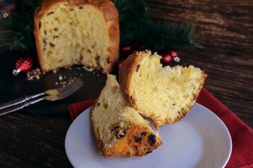 Panettone slices on the wooden table with  Christmas decoration and vintage forks. Traditional Italian cake for celebrate Christmas and New Year. Copy space.