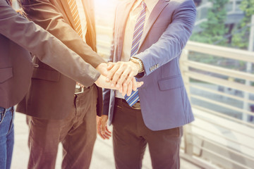 Success Teamwork Concept, Business people team with clipping path joining hands over blurred city background