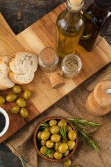 High angle view of olives and oils bottles with bread