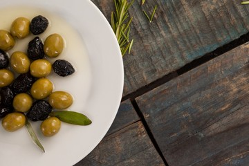 Overhead view of green and dry black olives with oil in plate