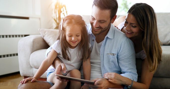 Family holding a tablet and looking at it