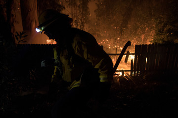 A firefighter fights a wildfire protecting a home's backyard, as strong winds carry a wildfire to Ventura, California