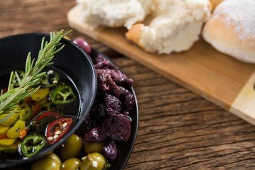 Pickled olives and vegetables with rosemary in bowl