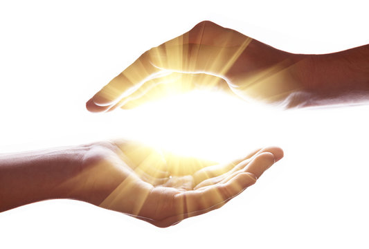 Woman hands protecting and containing bright, glowing, radiant, shining light. Emitting rays or beams expanding of center. Religion, divine, heavenly, celestial concept. White background copy space