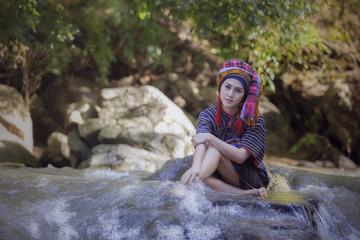 Karen woman sit on the rock in stream