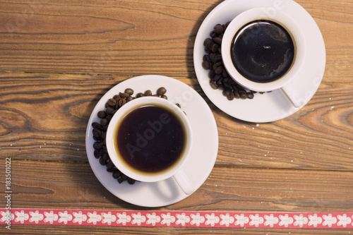 two coffee cups with coffee beans on saucers on a rustic wooden background a bottom