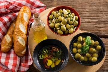 Marinated olives, bread and olive oil on heart shape board