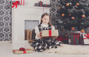 Beautiful girl unwrapping christmas presents