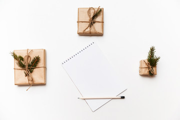 Empty notebook, pencil and gift boxes or presents packed in kraft paper isolated on white, top view
