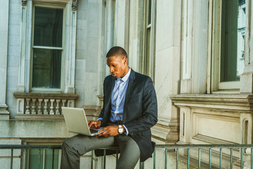 African American businessman working in New York. Wearing black blazer, wristwatch, a guy sitting on railing inside vintage style office building, looking down, reading, working on laptop computer..