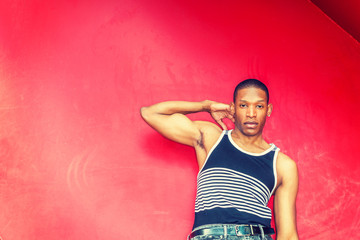 Summer Heat. Man casual fashion. Wearing black, white striped tank top,  raising arm, hand touching shoulder, young African American guy leaning against red metal wall, seriously looking at you.