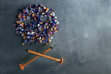 Tabletten und Spritzen formen ein Totenkopfsymbol
