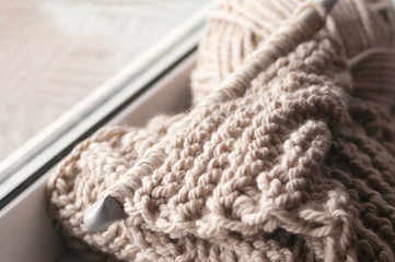 A knitted scarf with a thick thread on thick beige knitting needles. Close-up with blur.