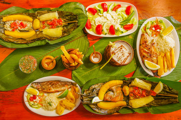 Above view of assorted food, grilled meat with potato, sweet tomatos, salad, pepper, fried plantain, fish in a leaf with yucca, fried fish, fried yucca, palmito salad, served in white plates over a