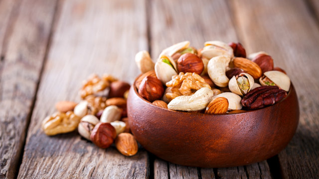 Nuts Mixed in a wooden plate.Assortment, Walnuts,Pecan,Almonds,Hazelnuts,Cashews,Pistachios.Concept of Healthy Eating.Vegetarian.Copy space.selective focus.