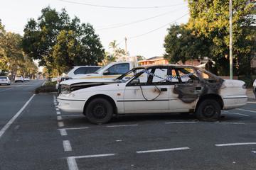 Ausgebranntes Autowrack auf Parkplatz