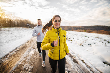 Poster Glisse hiver Beautiful happy active runner girl jogging with her personal handsome trainer on a snowy road in nature.