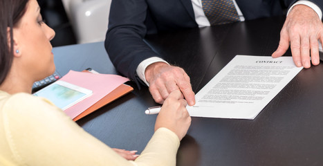 Woman signing contract with financial adviser