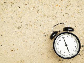 Alarm clock on beach sand, showing six o'clock