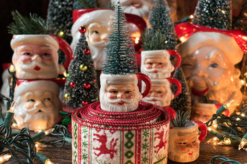vintage santa mug collection with wire brush Christmas trees and lights closeup