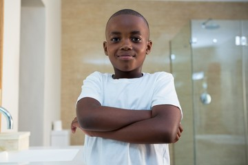 Portrait of smiling boy standing in bathroom