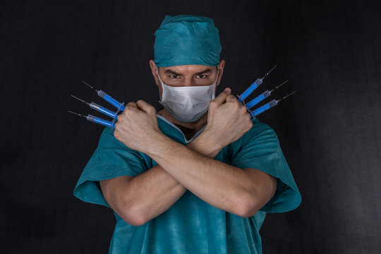 Surgeon in scrubs with syringes arms crossed on a black background