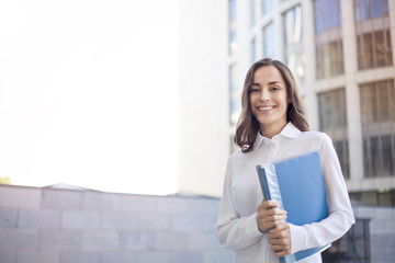 Portrait of happy beautiful business woman with documents in hands. Business building background