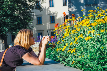 young woman taking photograps of yellow flowers with her smartphone