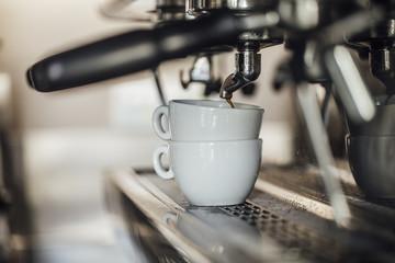 Cups of coffee on coffee maker machine.