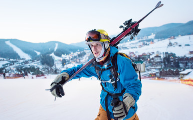 Close-up a guy skier in a blue jacket, a yellow helmet and glasses is holding sticks on his shoulder and staring into the distance against the backdrop of the ski resort
