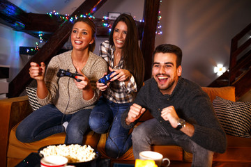 Two female best friends sitting at home on pleasant  evening and playing games on console.They challenge each other to win while man cheering.