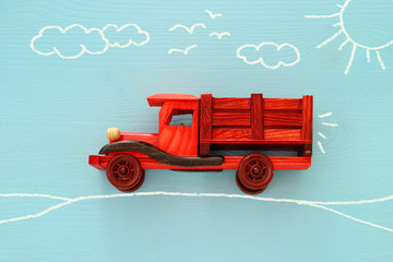 Concept of imagination, creativity, dreaming and childhood. Old wooden toy car with info graphics sketch on the blue background.