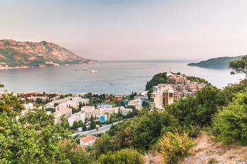 View of the beautiful bay, hotels and crowded beaches of the resort town of Becici in the rays of...