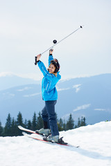 Cheerful woman skier wearing blue ski suit and black helmet, holding poles above a head, smiling to the camera, enjoying skiing at ski resort in the mountains. Ski season and winter sports concept