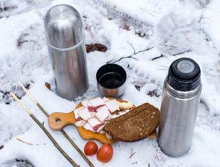 lard, bread, with tomatoes on a wooden cutting board in the snow next to the thermos with tea.