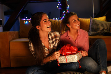 Two young woman opens a gift which they got from they friends.Celebration concept.