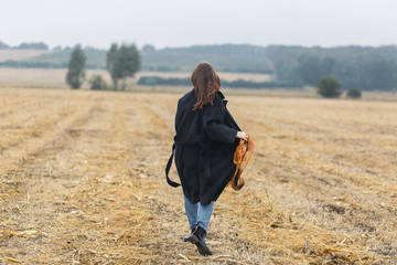 Rear view of caucasian brunette woman in black coat walking on field