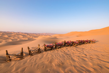 Landscape with wooden seats in the desert at sunrise.