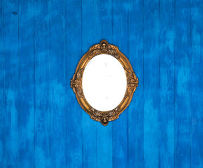 old Victorian decorative golden mirror on a blue wooden wall